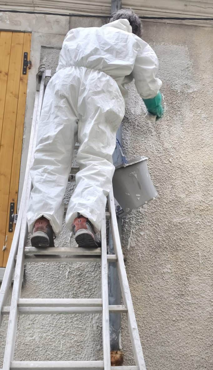 homme sur échelle nettoyant le crépi d'une façade